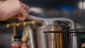 L'uomo sta utilizzando il dispositivo degli spremiagrumi e sta producendo il succo d'arancia fresco nella cucina o nel caffè archivi video
