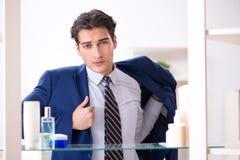 L'uomo sta vestendosi bene per lavoro in bagno Immagine Stock