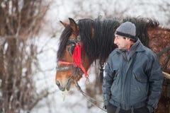 L'uomo sta vicino al suo cavallo Fotografia Stock