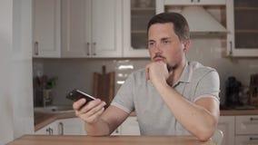 L'uomo stancato è cambiare canali di TV, facendo uso di telecomando, sedentesi alla cucina video d archivio