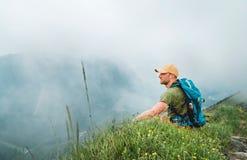 L'uomo stanco di viaggiatore con zaino e sacco a pelo ha una pausa che gode del fondo nuvoloso della valle che cammina dalla cate immagine stock libera da diritti