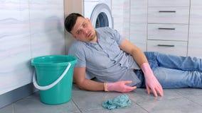 L'uomo stanco in guanti di gomma ha un resto da pulizia che mette sul pavimento della cucina video d archivio
