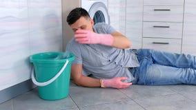 L'uomo stanco in guanti di gomma ha un resto da pulizia che mette sul pavimento della cucina archivi video