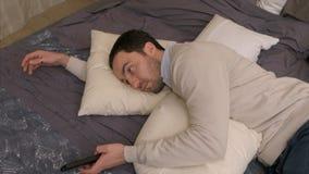 L'uomo stanco sdraia su un letto per riposare ed utilizza un telecomando per guardare la televisione Fotografia Stock