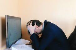 L'uomo stanco sta lavorando al computer confronta i grafici Fotografia Stock Libera da Diritti