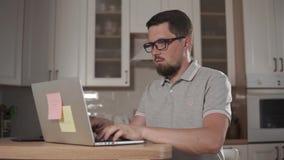 L'uomo stanco sta scrivendo su un computer portatile, sedendosi nella casa, eliminante i suoi vetri archivi video