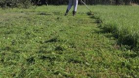 L'uomo in stivali falcia l'erba