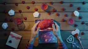 L'uomo strano ottiene il cuore umano di plastica come presente sconosciuto di festa, vista superiore stock footage