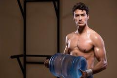 L'uomo strappato muscolare con la grande bottiglia di acqua Immagine Stock