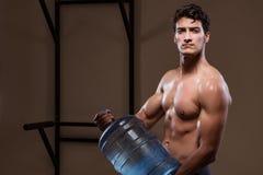 L'uomo strappato muscolare con la grande bottiglia di acqua Fotografie Stock