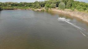 L'uomo su Jet Ski guida velocemente con molto spruzza sul fiume stock footage