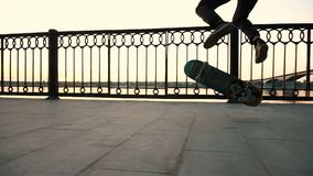 L'uomo su un pattino esegue una vibrazione del ollie - inganni il salto del kickflip su un bordo al tramonto, movimento lento archivi video