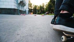 L'uomo su un pattino esegue una vibrazione del ollie - inganni il salto del kickflip su un bordo attraverso una fine di ostacolo  stock footage