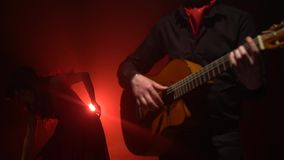 L'uomo sulla chitarra gioca un dancing della ragazza di flamenco Luce da dietro Fumi la priorità bassa stock footage