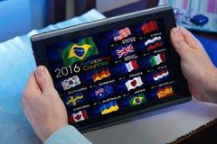 l'uomo sulla compressa che guarda un canale di Olympics mette in mostra sulla TV online Fotografie Stock Libere da Diritti