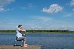L'uomo sulla vacanza sta riposando su una sedia e sta pescando sul lago fotografia stock libera da diritti