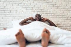 L'uomo svegliato felice è disteso a letto Fotografie Stock