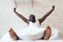 L'uomo svegliato felice è disteso a letto Fotografia Stock