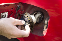 L'uomo svita il tappo del bocchettone di riempimento nell'automobile immagine stock