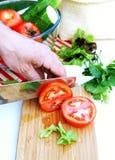 L'uomo taglia i pomodori maturi per l'insalata della verdura di estate Fotografia Stock