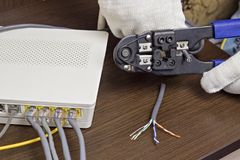 L'uomo taglia il cavo della rete, il modem sulla tavola, il router, il cavo della rete, un modem del primo piano fotografia stock libera da diritti
