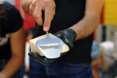 L'uomo taglia la fetta con un coltello del formaggio fotografia stock