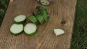 L'uomo taglia lo zucchini con un coltello archivi video