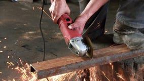 L'uomo taglia un fascio arrugginito del metallo, facendo uso di una turbina circolare Il rallentatore della smerigliatrice di ang video d archivio