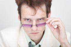 L'uomo terribile li esamina rigorosamente sopra gli occhiali Immagini Stock Libere da Diritti