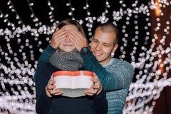 L'uomo tiene i suoi occhi dell'amica coperti mentre lei che dà un regalo immagine stock
