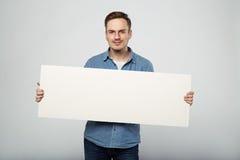 L'uomo tiene il bianco firma dentro un fondo di bianco dello studio Fotografia Stock Libera da Diritti