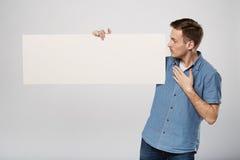 L'uomo tiene il bianco firma dentro un fondo di bianco dello studio Fotografie Stock