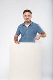 L'uomo tiene il bianco firma dentro un fondo di bianco dello studio Fotografia Stock