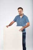 L'uomo tiene il bianco firma dentro un fondo di bianco dello studio Immagine Stock Libera da Diritti