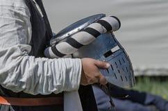 L'uomo tiene il casco medievale del ferro del cavaliere Fotografia Stock