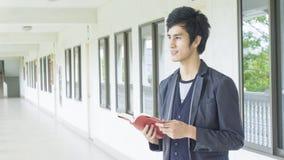 L'uomo tiene il libro rosso al corridoio Fotografie Stock Libere da Diritti