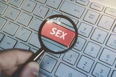 L'uomo tiene la lente d'ingrandimento sopra fornisce la chiave rossa con il sesso di parola scritta sui precedenti della tastiera fotografia stock