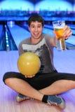 L'uomo tiene la sfera ed il vetro della birra Fotografie Stock