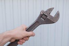 L'uomo tiene la vecchia chiave inglese nella mano Immagini Stock