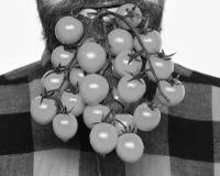 L'uomo tiene le bacche del pomodoro come barba isolata su fondo bianco Concetto d'agricoltura e di giardinaggio L'agricoltore tie Fotografia Stock