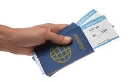 L'uomo tiene un passaporto ed i biglietti di aeroplano in sua mano Isolato su bianco fotografia stock