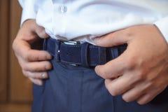 L'uomo tiene una mano sulla cintura nera Fotografia Stock
