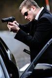 L'uomo tira una pistola in automobile Fotografie Stock Libere da Diritti