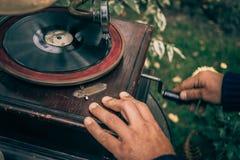 L'uomo torce una penna su un grammofono d'annata per giocare la musica, retro tonificato Fotografie Stock