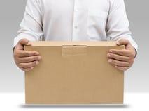 L'uomo trasporta la casella di carta marrone Immagine Stock