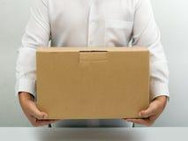 L'uomo trasporta la casella di carta marrone Immagini Stock