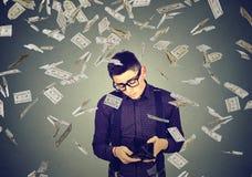 L'uomo triste che esamina il suo portafoglio vuoto sotto le banconote del dollaro dei soldi piove Fotografie Stock