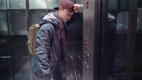 L'uomo triste ha avvertito lo sforzo e discende nell'elevatore nel sottopassaggio archivi video