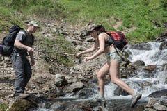 L'uomo turistico aiuta un ragazza-turista al fiume d'attraversamento della montagna Immagini Stock