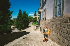 L'uomo turistico del ` s sta con il suo di nuovo alla vecchia città europea di Bergamo in Italia di estate Vestito in uno scialle Immagini Stock Libere da Diritti